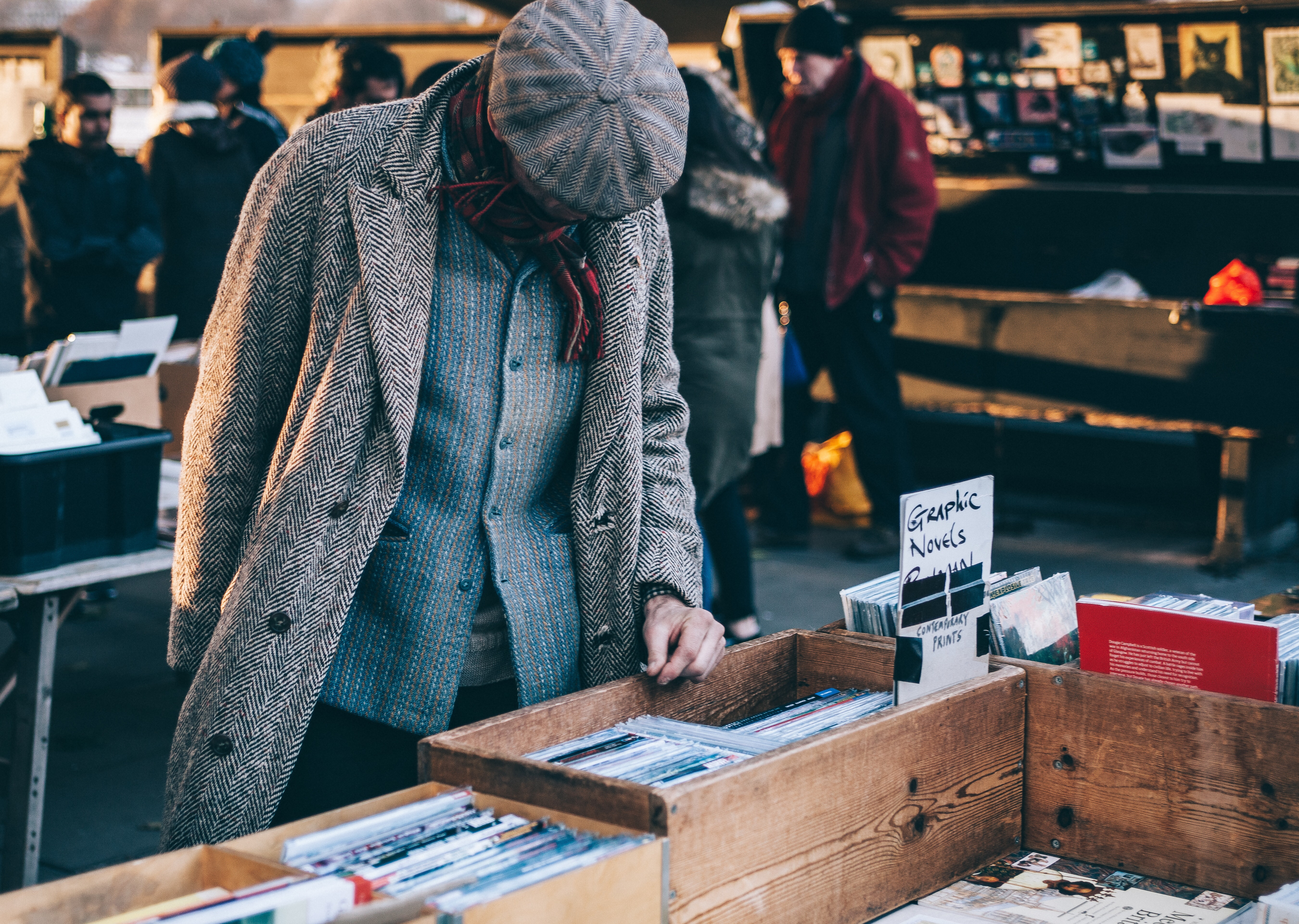 Man in a coat looking through boxes of used novels to save money