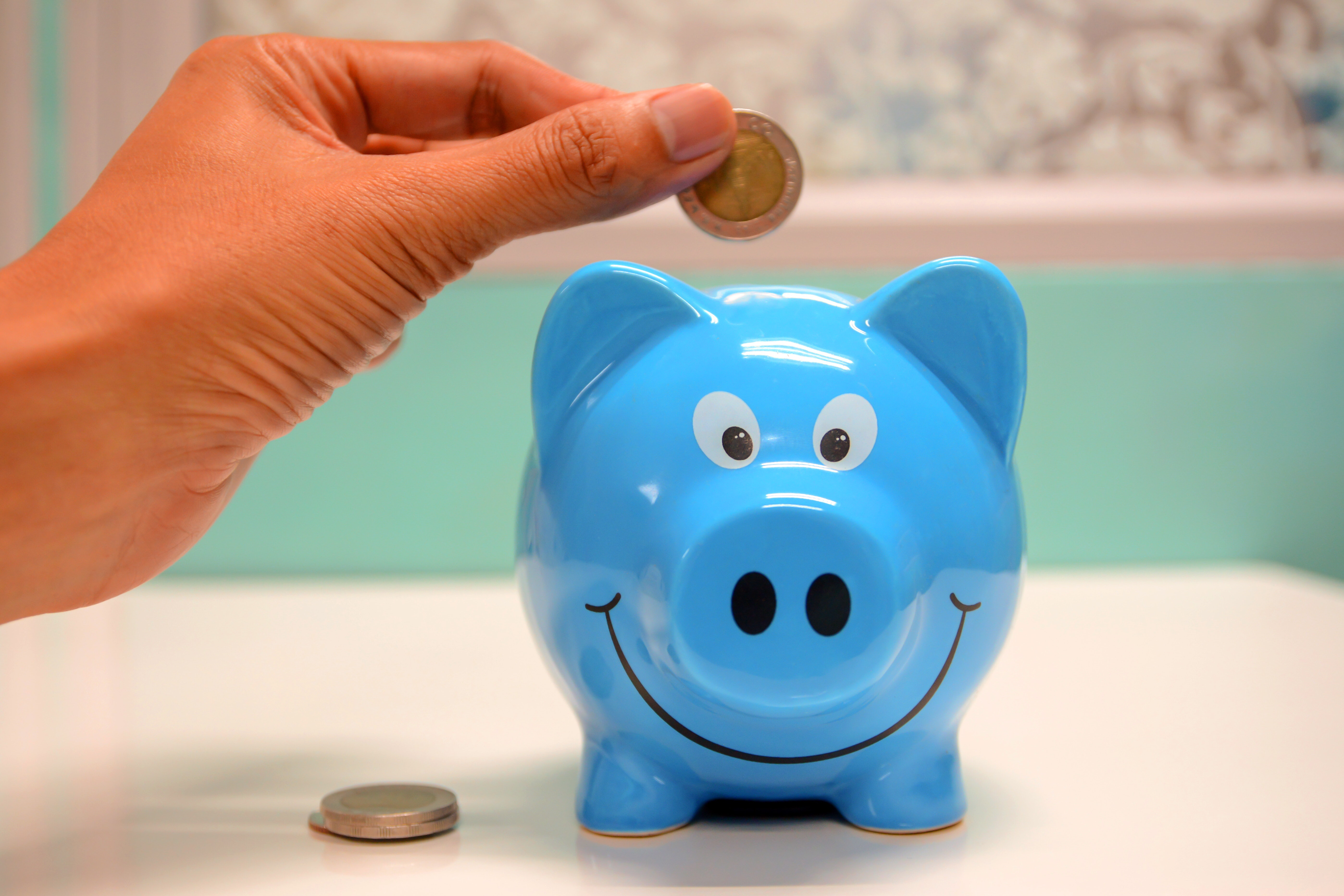 Blue piggy bank with someone depositing a coin to save money
