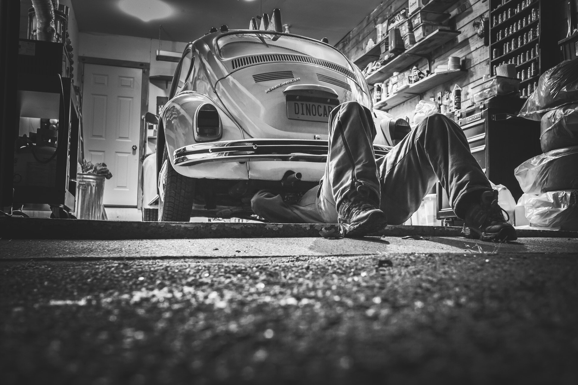 Black and white photo of  mechanic saving money by doing his own repairs
