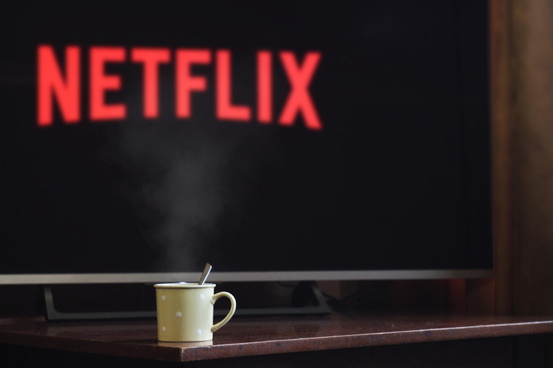 Cup on a table in front of a Netflix loading screen