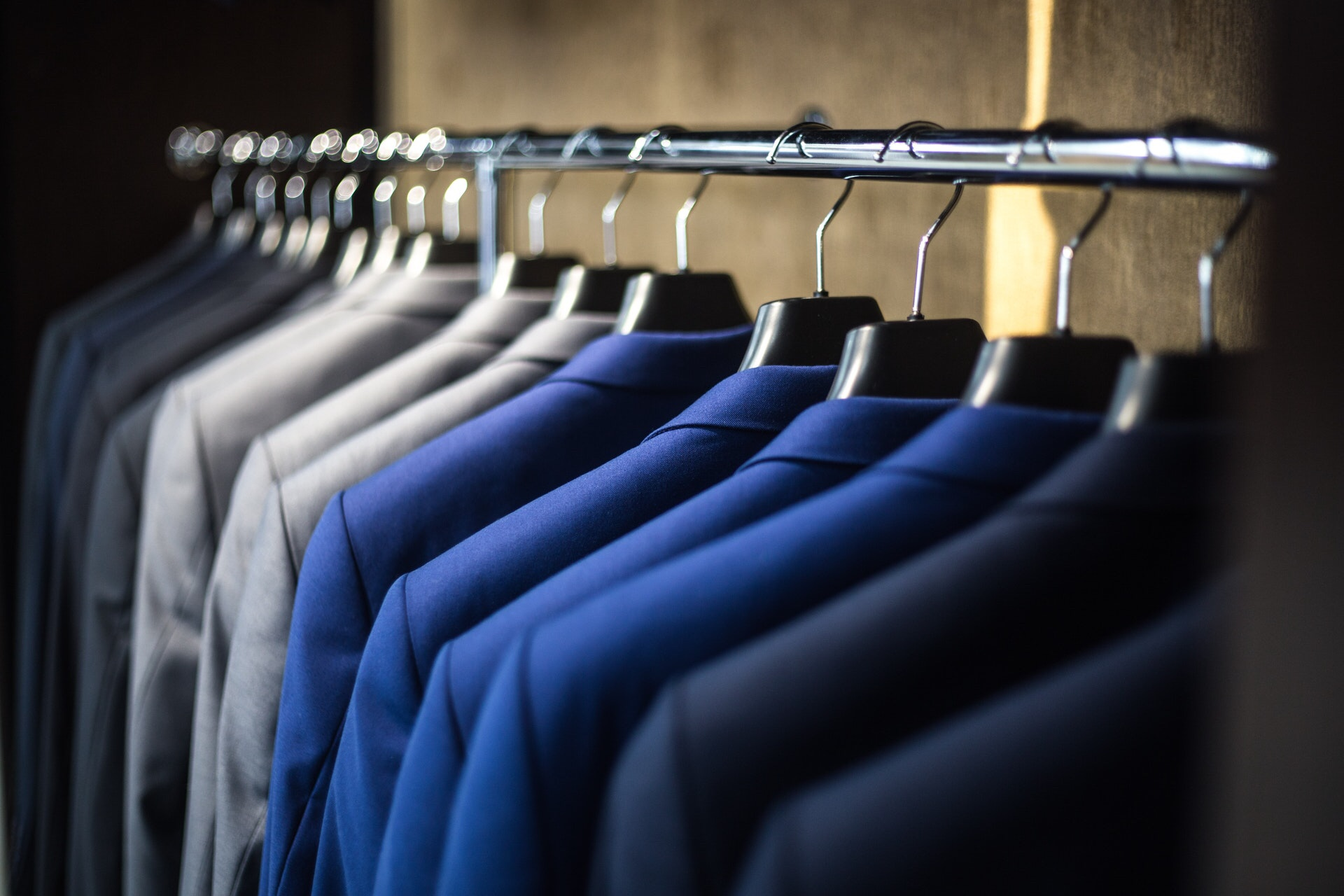 Neatly organized closet of various suits