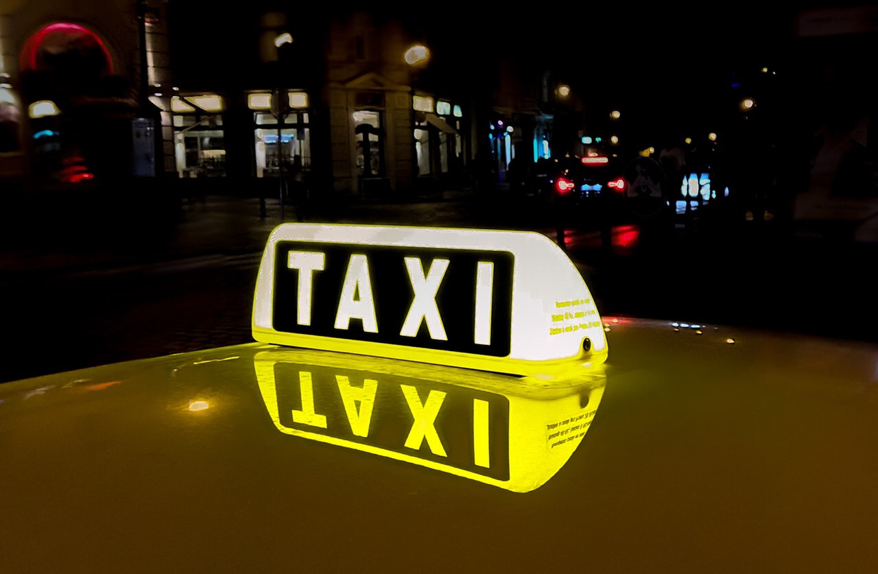 Lit taxi sign in a downtown city at night