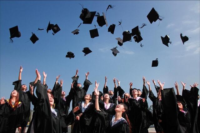 College graduates throwing caps