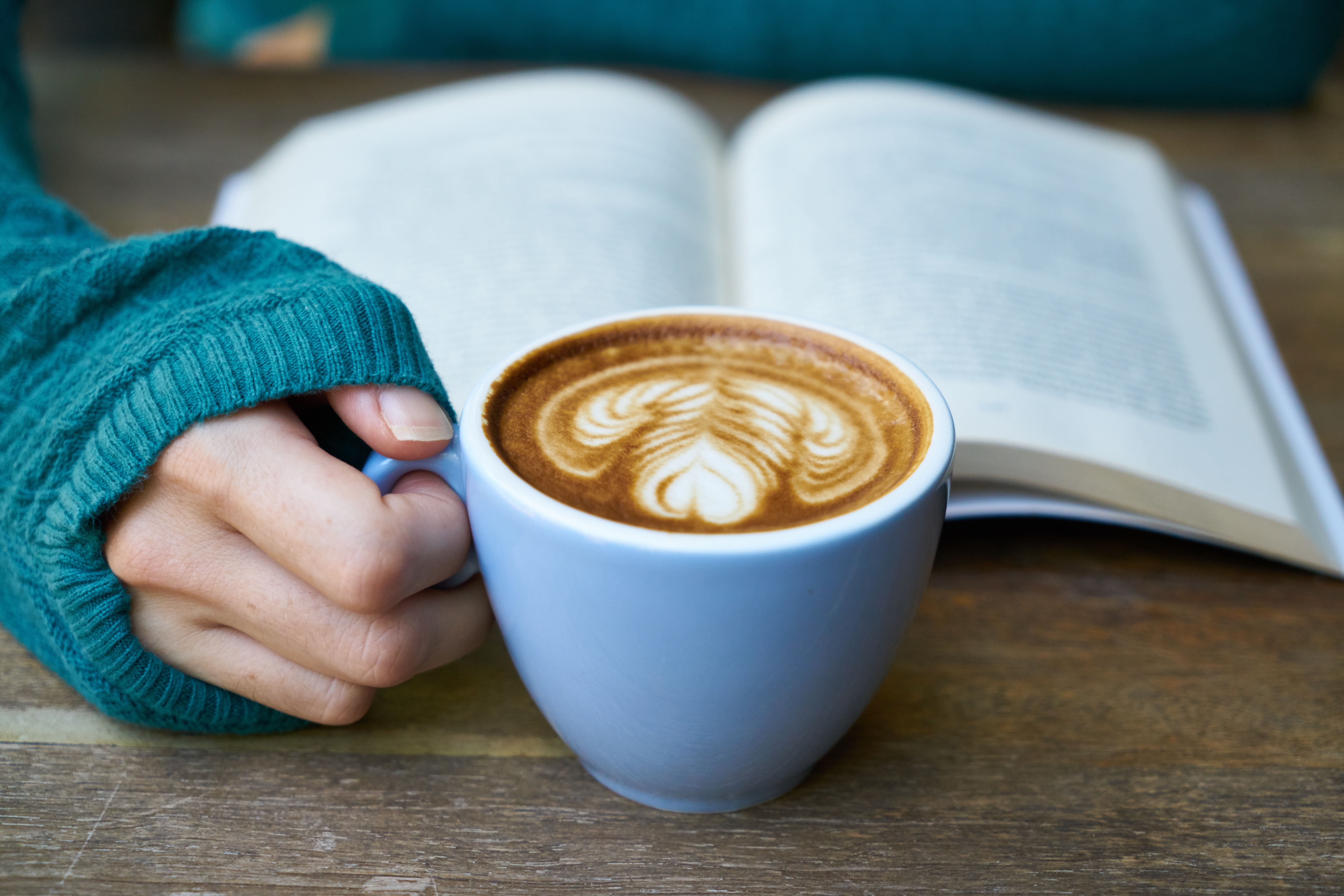 Reading a book while holding coffee